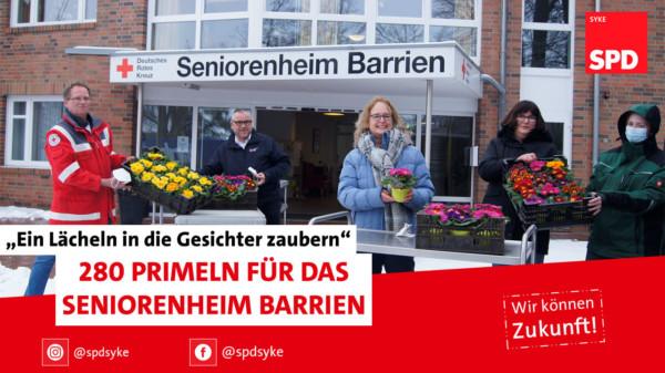 SPD-Mitglieder mit Primeln vor dem Seniorenheim